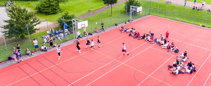 Overhead shot of an outdoor basketball game with spectators